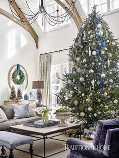 A gracious tree is dressed with blue and white ornaments and ribbons to coordinate with the living room's palette. - Photo: Emily Jenkins Followill / Design: Amy Morris