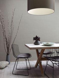 Chaises Bertoia noires associées à une table de repas en bois brut