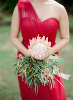 Protea bouquet + pretty one-shoulder red bridesmaid dress: Photography : Aria Studios Read More on SMP: http://www.stylemepretty.com/little-black-book-blog/2016/06/30/red-hawaiian-wedding/