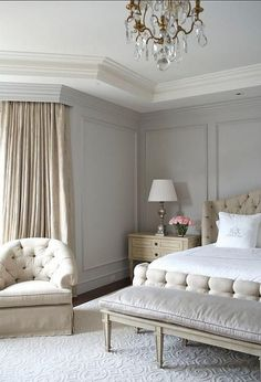 Beige and gray bedroom features gray walls painted Benjamin Moore Wickham Gray accented with gray trim lined with a beige tufted bed dressed in white and gray monogrammed bedding placed next to a warm gold French nightstand.