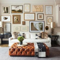 Framed Art Gallery over White Sofa with Leather Ottoman and Grey Rug | Studio Gild