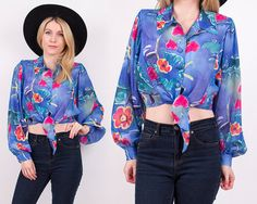 Vintage 80s blue abstract cropped blouse. Poet sleeves. Buttons up the front and ties at the waist. Abstract floral sun and hearts design.
