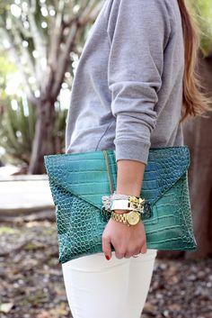 Casual look with a pop of colour - white jeans, grey sweatshirt and emerald green clutch as well as some arm candy!