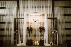 Draped fabric, antique window frames, and romantic candlelight create an elegant ceremony backdrop   Image by Ariana Tennyson Photography