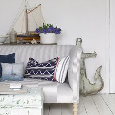 A living room with white wood plank floors, a blue-and-white striped couch, white walls, and nautical accents