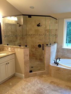 Frameless corner glass shower. dual shower heads. garden tub. tiled shower                                                                                                                                                     More