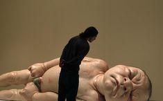 A man looks at a sculpture titled