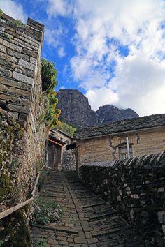Stone path and houses in Papigo village under the peaks of Astraka in the slopes of Timfi mountain (Zagori, Epirus, northwestern Greece).