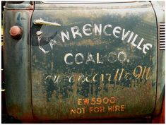 Old, worn hand-lettering on a truck door.