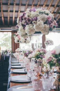 These tall wedding centerpieces had white lavender dusty plum flowers on a long wood farm table.  It is the perfect wedding flower arrangement inspiration!