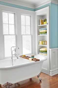 A double-ended Victoria + Albert claw-foot tub, cast from a durable blend of resins and volcanic limestone, offers a lightweight alternative to traditional cast iron. Here, it's staged beautifully against a bright window with towels and bath needs displayed within reach. | Photo: Wendell T. Webber | thisoldhouse.com