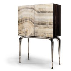 Onyx marble vanity cabinet with macassar ebony structure on cast metal stand. Doors of cabinet with inlaid steel structure and Onyx as pictured with 180 degrees opening system. Legs of cabinet in mirror polished cast metal with tips of legs in satinised metal finished in either Bronze, Golden or Black Nickel finish.