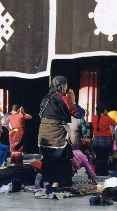 Tibetan Buddhists making prostrations outside The Jokhang Temple. Lhasa, Tibet.