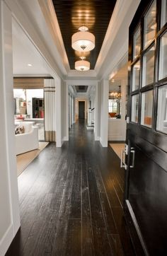 Love the glossy black bead board tray ceiling in this entry w/ the black front door.  Dark wood floors, drum pendants, w/white walls and neutral furniture.