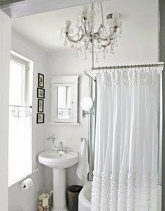 Shabby chic white bathroom design with crystal chandelier and ruffled white shower curtain.