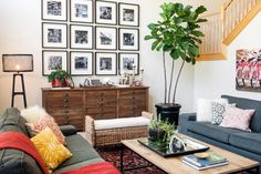This living room is far from boring. The gallery wall with black and white photos has real impact, as do the punched-up pillows and colorful art. Keeping neutral sofas in the room allows the accessories to sing, and plants add a breath of life that completes the space.
