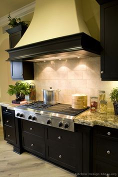 """Black Friday"" Kitchen: Luxury black cabinets with a large wood hood over a pro cooktop."