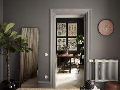 Gråmålade väggar, Mole's breath från Farrow & Ball. Spegel på golvet och fiolfikus på stam.