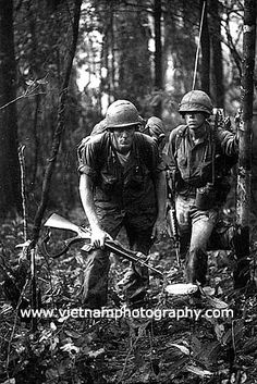 A sergeant and his radio operator (RTO) pause on the side of Chu Pong Mountain in the Ia Drang Valley during the summer of 1966. They were with the 1st Cavalry Division.
