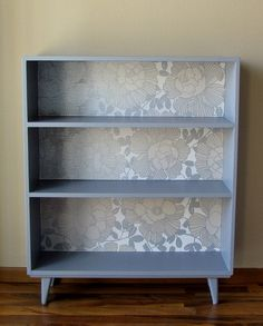 office. get two basic bookcases, attach feet, paint, back with cool wallpaper, and put on each side of desk for storage.