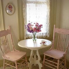 Chippy pink chairs paired with cream table. Lace curtains add to the cottage charm