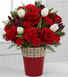 Christmas Comforts Rose & Tulip Flowers - 13 Stems - VASE INCLUDED. The Christmas Comforts Rose & Tulip Bouquet brings you home for the holidays with just one glance! Gorgeous red roses, red carnations and mini carnations are highlighted with white tulips and accented with lush holiday greens to create a simply stunning flower bouquet. Presented in a red ceramic vase showcasing a winter plaid rim, this flower arrangement makes a wonderful hostess gift before or after your holiday…