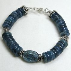 "Handmade gemstone kyanite bracelet features a strand of semi-precious disc kyanite gemstones, sterling silver beads, wire band, and hook clasp. 8"" in length. Add a necklace, pendant and earrings to co"