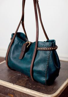 SHOP - cibado The Blue Stud - Blue Buffalo leather bag, this is a 1 off bag, completely hand stitched with waxed thread and old horse tack are re - purposed here as handles, true buckle closure also off of old horse tack and vintage studded pieces decorate the pleated gussets.