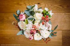 Vrolijk bruidsboeket in crème tinten met rode accenten. Wedding bouquet in creamy shades with red accents.
