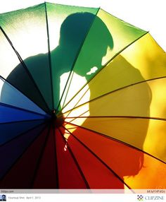 Engagement Announcement...the happy couple in silhouette behind an almost transparent rainbow colored umbrella...Faith and Love