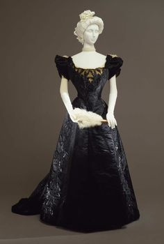 "Evening gown in two pieces (bodice and skirt) in black silk satin and lace. ""En couer"" bodice embroidered in leaves motifs with glass straws and beads; Atelier Worth, Paris, 1897-1899 ca. Collection..."