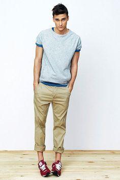 Opta por una camiseta con cuello circular gris y un pantalón chino marrón claro para cualquier sorpresa que haya en el día. Haz este look más informal con deportivas rojas.