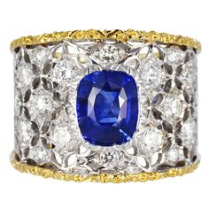 Two tone 18 karat yellow and white gold open work ring consisting of 1 cushion cut blue sapphire weighing approximately 1.40 carats set with 1.00 carats total weight of full cut diamonds accents, signed M. Buccellati. 20th-21st Century