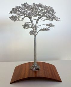 Using nothing but wire, sculptor Clive Madison creates tangled trees that grow from wooden bases into dense clusters of leaves and branches. Each piece is made by hand without glue or solder, using single strands of wire that start at the base and terminate at the top. Yo