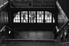 sybway station Berlin Eberswalder Strasse - Subway station Eberswalder Straße Berlin. View from the platform down the stairs. Through the windows you can see the people on the street. Black white street photography from Berlin.