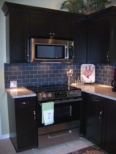 love the dark cabinets, stainless steel appliances and grey subway tile