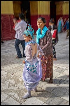 Youth, Protector Of The Old by Jon Sheer -Young girl and grandmother (?) at a festival inside Mahamuni Pagoda in Mandalay, Myanmar.