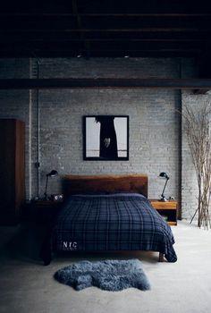 A parede de tijolinhos aparentes compõe o ambiente com madeiras e cores em tons de azul.