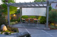 Small LED Spot Fixtures Above A Dining Table Produce Subdued Lighting For Nighttime Entertaining. Aluminum Lamps Were Installed Along Pathways For Safety. Background Fence Lighting Offers Depth and Dimension.  -Garden Design #Patio