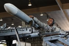 U.S. Air Force Staff Sgt. Ryan Baldwin, 13th Aircraft Maintenance Unit weapons load team chief, unloads an AIM-120 Advanced Medium-Range Air-to-air Missile to be put on an F-16 Fighting Falcon during the Load Crew of the Quarter competition at Misawa Air Base, Japan, Oct. 18, 2013. The three-man crew teams loaded an AGM-88 High-speed Anti-radiation Missile, an AIM-120 AMRAAM, and an AIM-9 Sidewinder, a short-range air-to-air missile. (U. S. Air Force photo by Senior Airman Derek VanHorn)