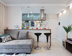Soluções criativas, como o uso de espelhos na sala e a integração desse ambiente com a cozinha, deram mais espaço ao apartamento