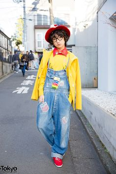 P-chan from the Tempura Kidz on the street in Harajuku wearing a bow hat, Snoopy bow tie, glasses, denim overalls, and a Ronald McDonald backpack. Full Look