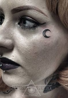 Small moon tattoo next to the left eye.