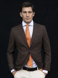 Spread collar. Brown jacket. Orange tie.