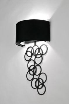 Huis decoratie interieur verlichting .  Prachtige wandlamp in mat zwart metaal met een mat zwarte stoffen kap. Onder de kap hangt een asymmetrisch geheel van zwarte ringen. Achter de buitenste kap zit nog een kleinere kap zodat inkijk in de lamp wordt voorkomen. Voor woon keuken woonkamer of slaapkamer . Hoogte: 56,5 cm Breedte: 30 cm www.rietveldlicht.nl