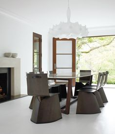 """Konstantin Grcic's Venus chairs for ClassiCon surround a table by Poliform in the formal dining room. Hill selected the Flos chandelier designed by Marcel Wanders for its """"Old World reverence."""" The sleek fireplace mantel was designed by Hill and cobbled together onsite from three solid slabs of limestone.  Photo by: Gregory Miller"""