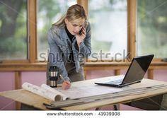 A young woman is looking at a laptop and talking on the phone.  She is working at a construction site.  Horizontally framed shot. - stock photo