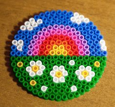 Awesome rainbow, flowers & grass coaster from perler /Hama beads Easy Perler Bead Patterns, Melty Bead Patterns, Diy Perler Beads, Perler Bead Art, Pearler Beads, Fuse Beads, Beading Patterns, Hama Beads Coasters, Embroidery Patterns