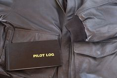 a leather aviator jacket and pilot log book