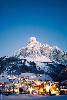 Landscape: small alpine village under snow covered mountain peak, at night, winter. Italian alps, Dolomites, Italy by Matteo Colombo